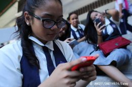On 11 March 2016, Jan, 16, a student at St. Francis of Assisi School, and other girls, check their smart phones after classes in the Central Visayas city of Cebu, Philippines. Social media is a huge influence in children's lives and being constantly connected to the Internet also comes with many risks, including online sexual exploitation, of adolescents and children. After the loss of her grandfather, together with the pressures of adolescent life, Jan battled depression, and was a victim of cyber-bullying. Like many adolescents s, she turned to the Internet for help. She saw a social media post about 'cutting,' a form of self-injury, and how the post described it as being an effective way to deal with pain and she tried to take her own life. She sought help from a UNICEF-supported programme on CyberSafety providing guidance and training in social media and she now works with UNICEF to help educate her peers about online safety. Worldwide, children make up one-third of all Internet users. With the rapid expansion of information and communication technologies, protecting children online is an urgent global priority. Among Filipino youth, more than half regularly use the Internet on own devices with easy and unrestricted online access. The lack of awareness of online safety, along with children's natural inquisitiveness, adolescent sexual curiosity and susceptibility to peer influence, makes children vulnerable to online violence, sexual abuse and exploitation. This can manifest itself in cyberbullying, sexual solicitation online, and victimization through child sexual abuse material and live stream child sexual abuse. Online sexual abuse and exploitation may involve both contact and non-contact offenses, and often involves subtle forms of manipulation in which a child is coerced into these situations without being able to fully comprehend what is happening to them or give informed consent. While poverty in the Philippines, and a culture of silence in re