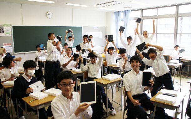 教室で配付されて盛り上がる生徒たち