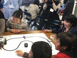 児童とともにプログラミングでロボットを操作する高市総務大臣