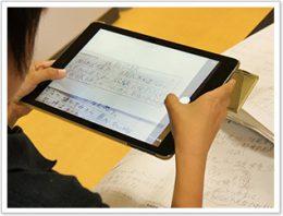 iPadでノートを撮影して、MetaMoJi ClassRoomに写真を取り込む児童。