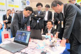プログラミング教育ロボットの説明を聞く参加者