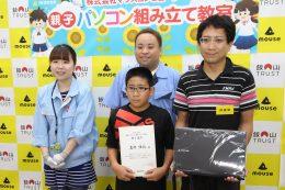 修了証とパソコンを手にする組立完了第1号の岩井さん親子と先生と校長
