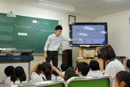 黒板、大型モニター、タブレットを使った音楽の授業