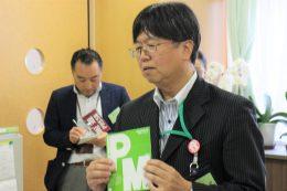 「PM」パンフレットを手に説明する松野校長
