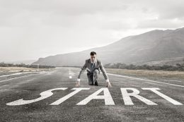 Young businessman in start pose on road ready to run